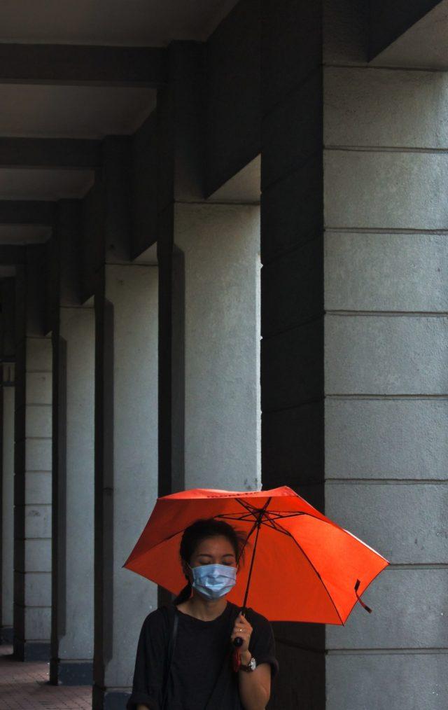 Chinka w maseczce i pod parasolem